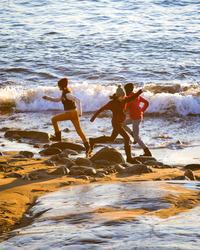 Skolebørn leger i skumringen langs havet ved en lille strand i Nuuk.