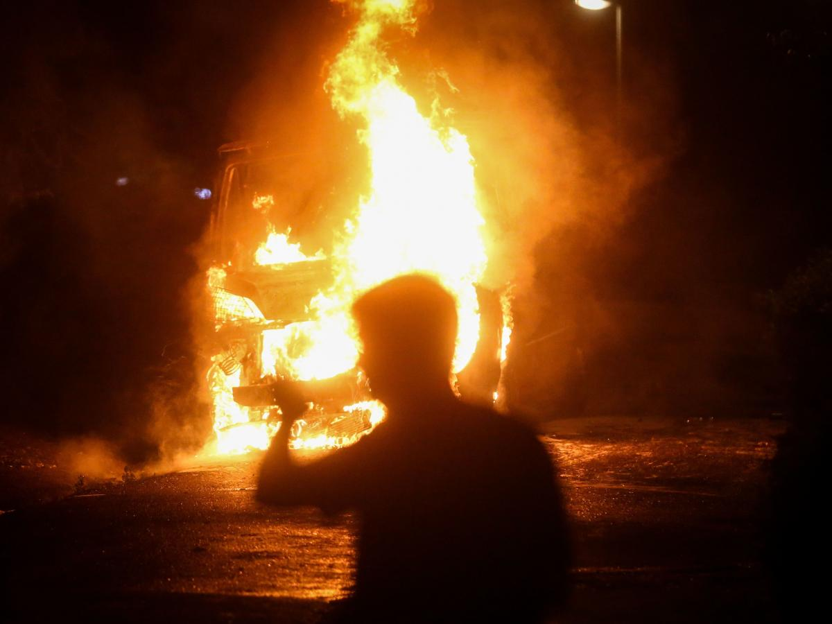A man passes a burning police vehicle during a rally Tuesday that descended into clashes between police and protesters in Belgrade.