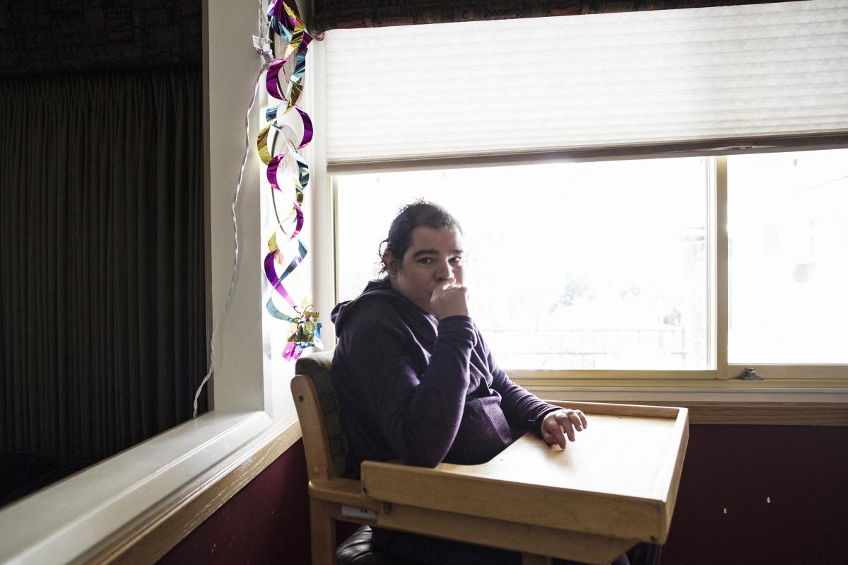 """Natalie waits for lunch at the home she shares with her family in Northern California. In 2011, her family could tell something was wrong. She was in pain and couldn't sleep at night. """"There was something she couldn't tell us,"""" her mother, Rosemary, says."""