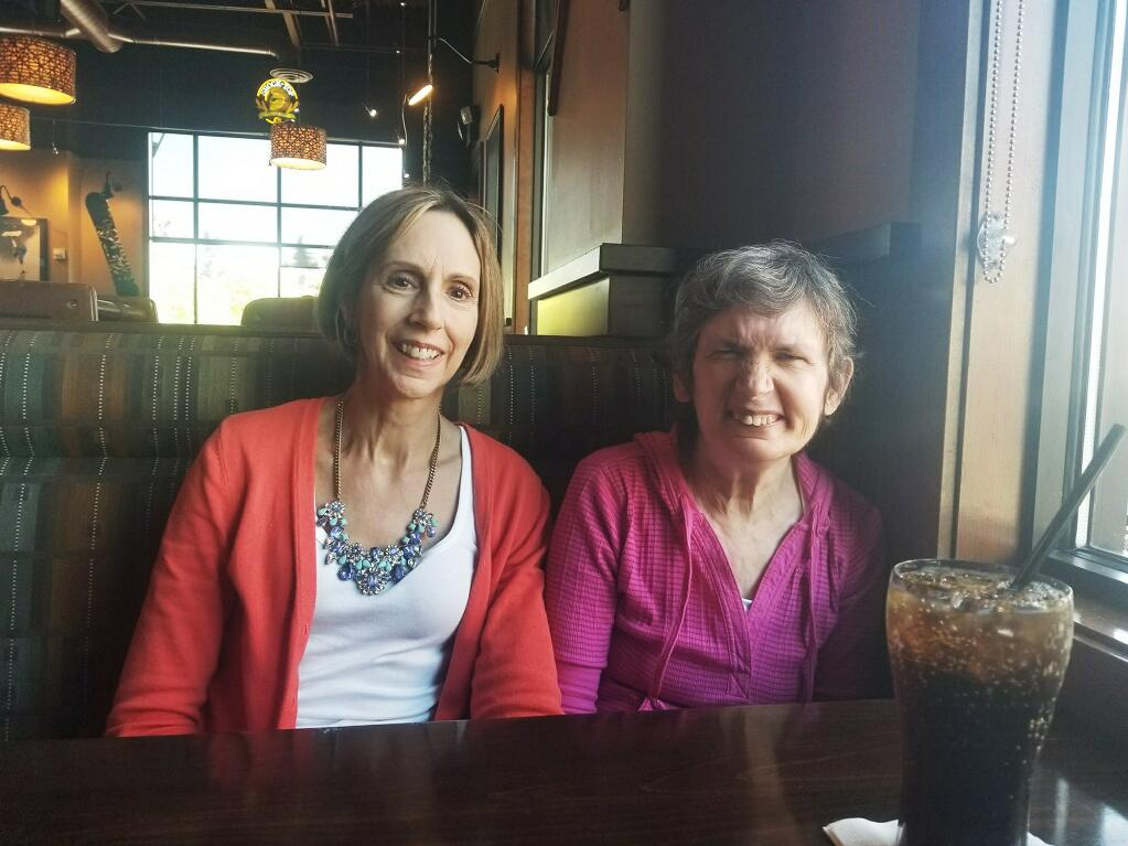 """Cathy McIvor (left) takes her sister, Maryann, out for a hamburger in Tacoma, Wash. """"Hamburger"""" is one of a few dozen words Maryann can say with sign language."""
