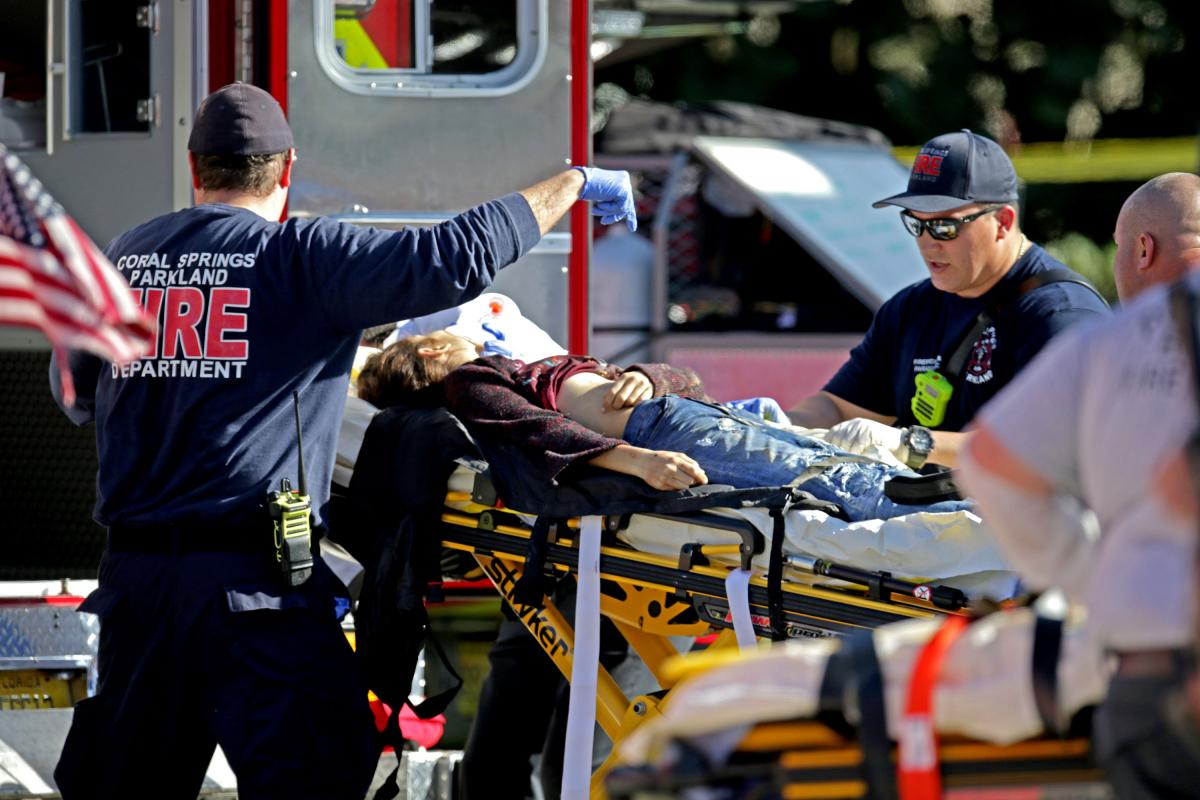 Medical personnel tend to a victim outside the school.
