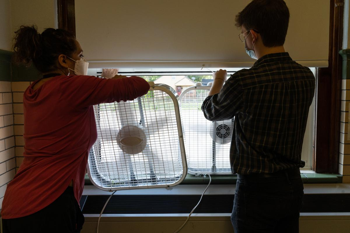 Quesada and student teacher Christopher Wolfzorn place box fans in open windows to keep air circulating. After doing her own research, Quesada decided to face one fan outward and one fan inward for better circulation.