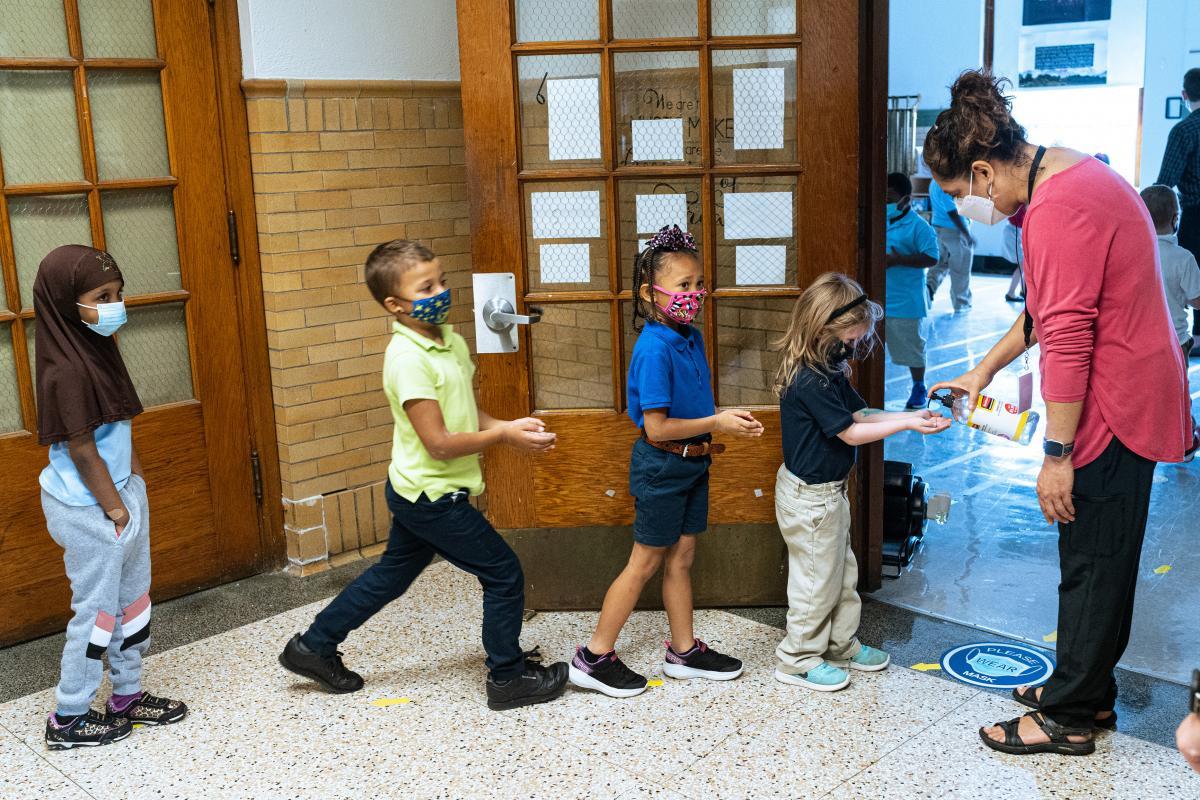 Quesada greets her second grade music class and gives them each a squirt of hand sanitizer as they enter her classroom.