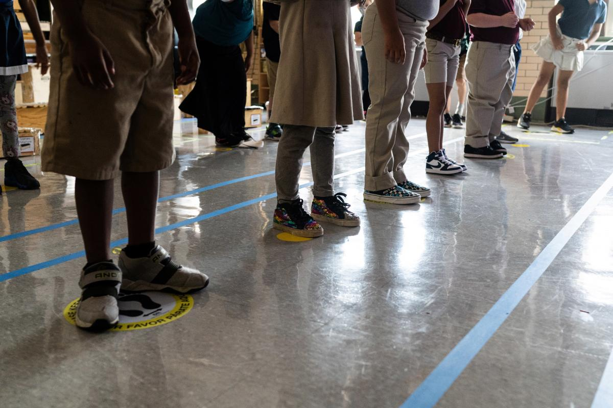 In order to keep them as separated as possible, students in Quesada's third grade class stand on carefully placed stickers on the floor. Because of the space instruments take up, and the need for students to be able to see their teacher, there's often onl