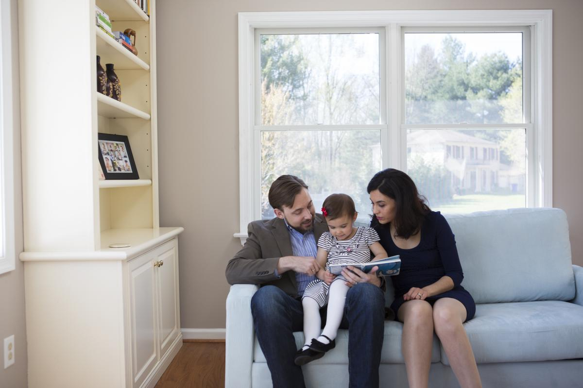Travis and Sadiye Rieder read a book with their 2-year-old daughter, Sinem, in their Maryland home. Travis is a philosopher and ethicist who argues against having too many children, for moral and environmental reasons. His wife always wanted to have a big