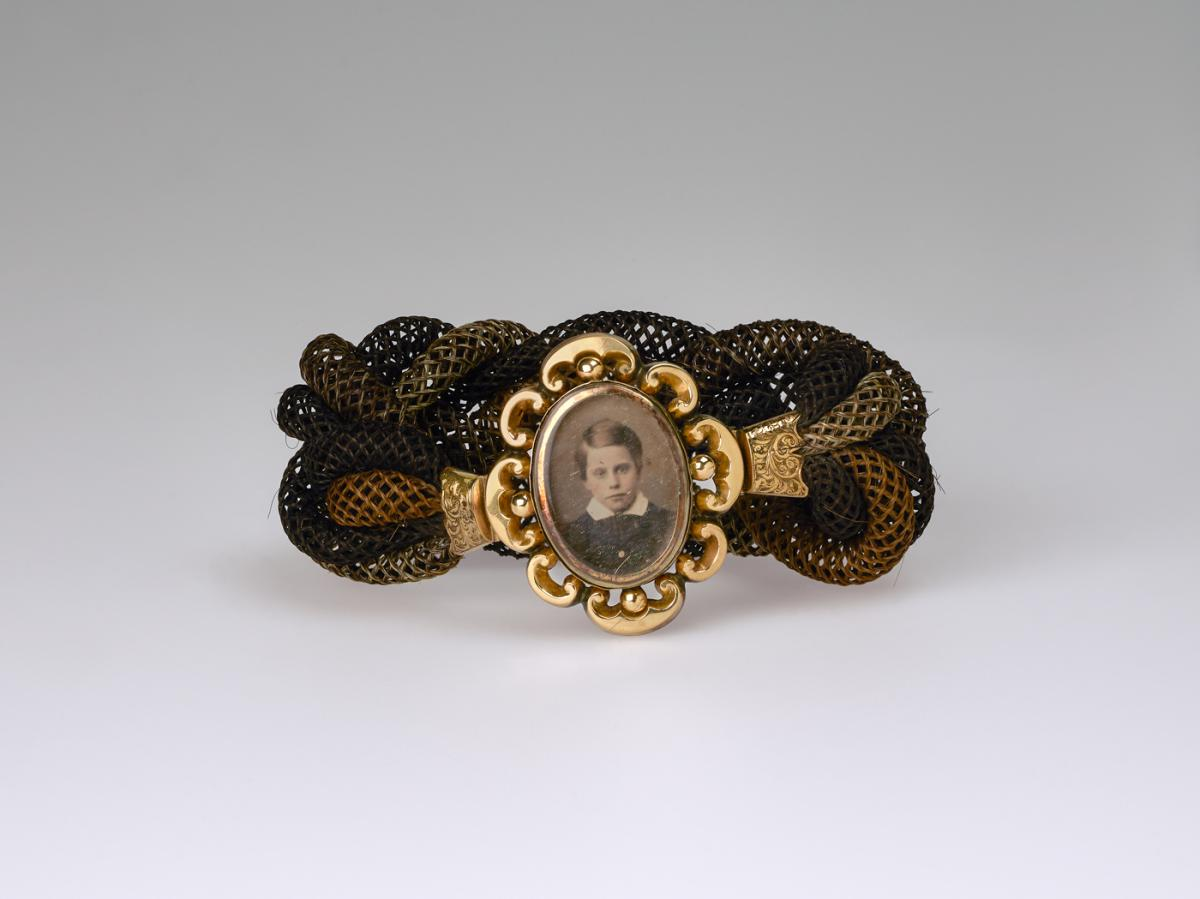 Unidentified artist, Untitled (hair band, young boy), ca. 1865, daguerreotype, woven hair, metal fittings. Smithsonian American Art Museum, the L. J. West Collection of Photographic Jewelry, Museum purchase made possible through the Franz H. and Luisita L