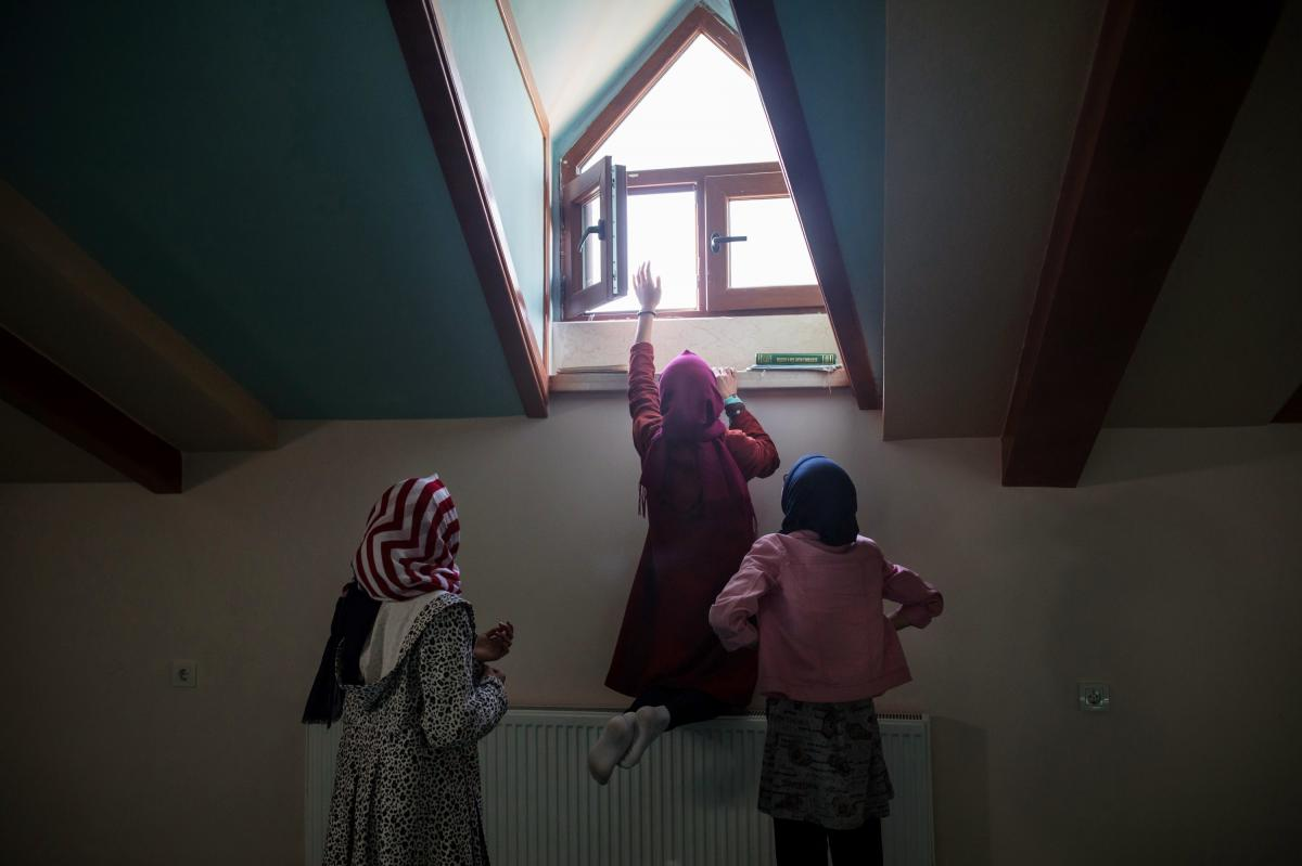 A student opens a window inside the school's mosque before the start of afternoon prayers. The school was built in 2017 and originally was expected to be a private institution where parents would pay tuition. The school's founders changed its mission afte