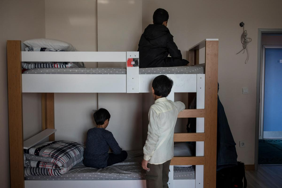 Friends Nurzat (bottom left) and brothers Abdulla (standing) and Muhammet (top) spend time in a dormitory room at the boarding school.