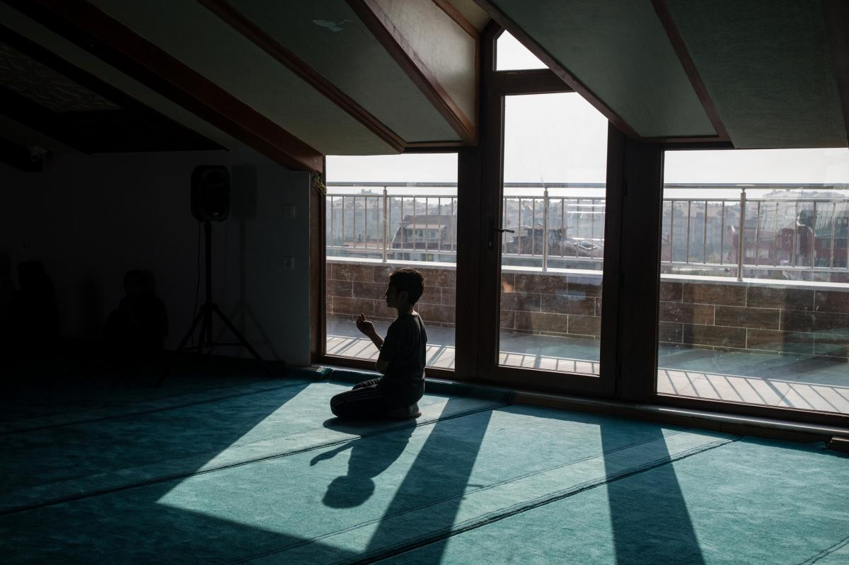 A boy prays inside the Oku Uygur boarding school's mosque. The Oku Uygur boarding school grew out of the Uighur-language classes that its founder, Habibulla Kuseni, previously ran from his apartment.