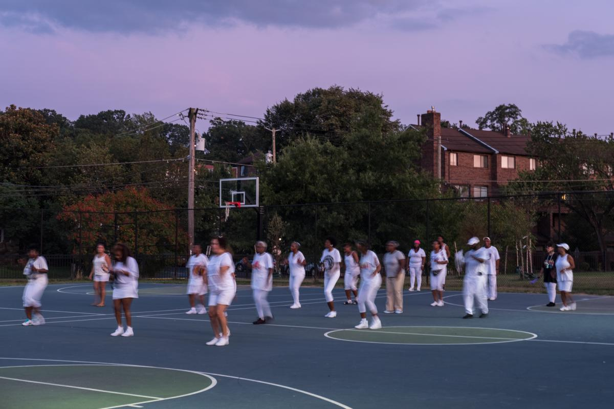 """The Addicts take to the basketball court to perform during the social. '""""The appeal is togetherness,"""" Allen says."""