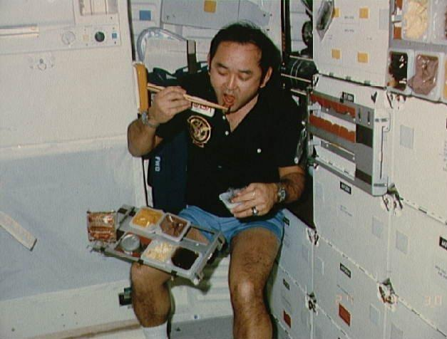 Mission specialist Ellison S. Onizuka takes a meal break on the mid-deck of the Discovery space shuttle during the STS 51-C mission in the 1980s.