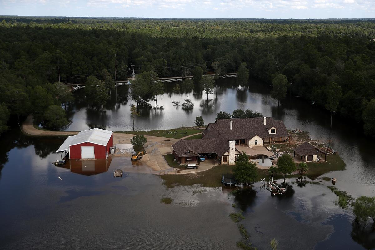 A Beaumont, Texas home surrounded by floodwaters in 2017. Places with less population density or less wealth are often less likely to receive federal flood mitigation funds.