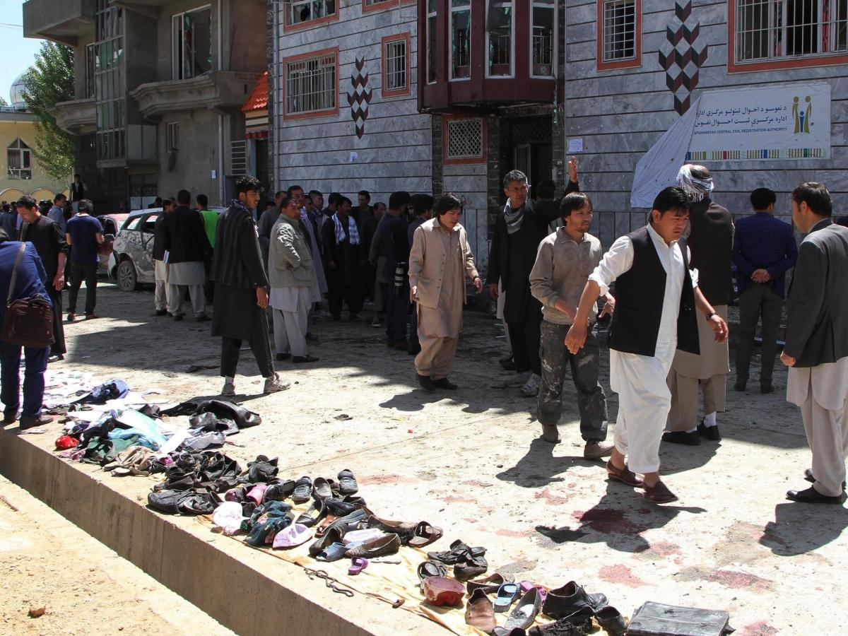 People gather around the scene of a suicide bomb attack that targeted a voter registration center in Kabul, Afghanistan on Sunday.