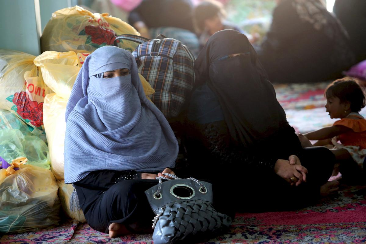 Sunni women who fled violence in Iraq's western province of Anbar settle at a mosque in Baghdad in April. Many Sunnis have moved out of areas controlled by the Islamic State, a Sunni extremist group. However, the displaced Sunnis are often treated with su