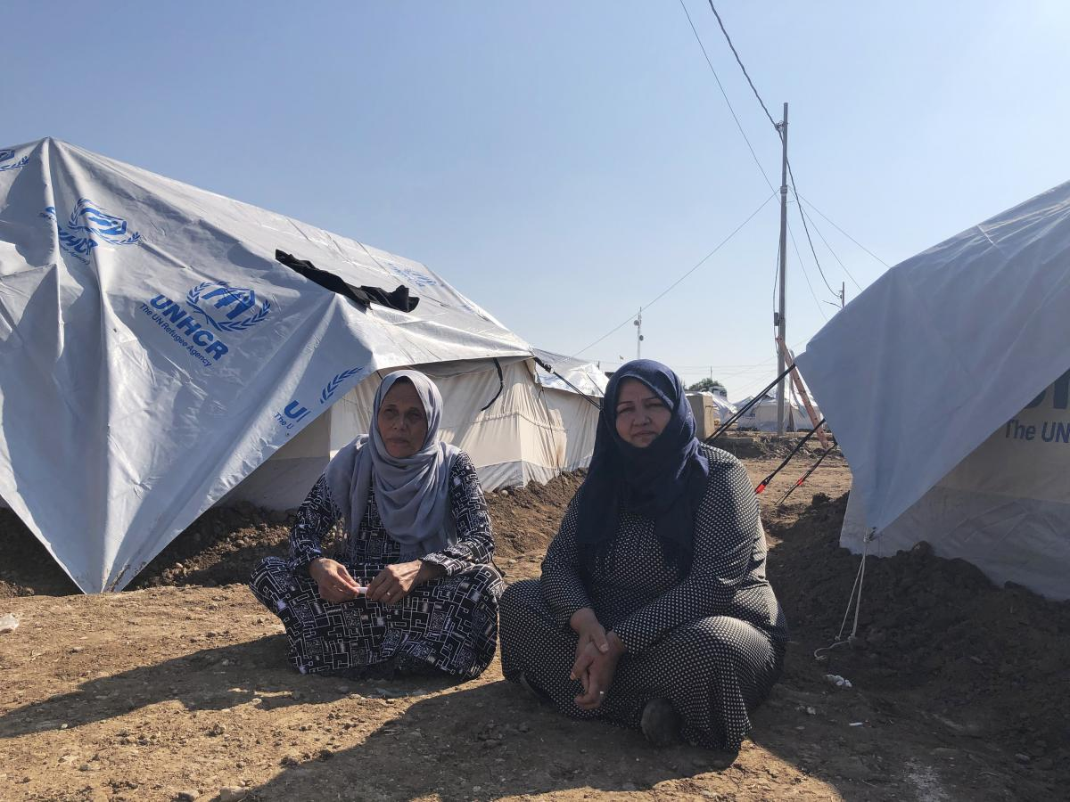 Wasfiye Jalal al-Din (left) sits outside her tent at the Gawilan refugee camp. She says the family fled the Syrian city of Qamlishi after Kurdish forces began storing weapons in their home.