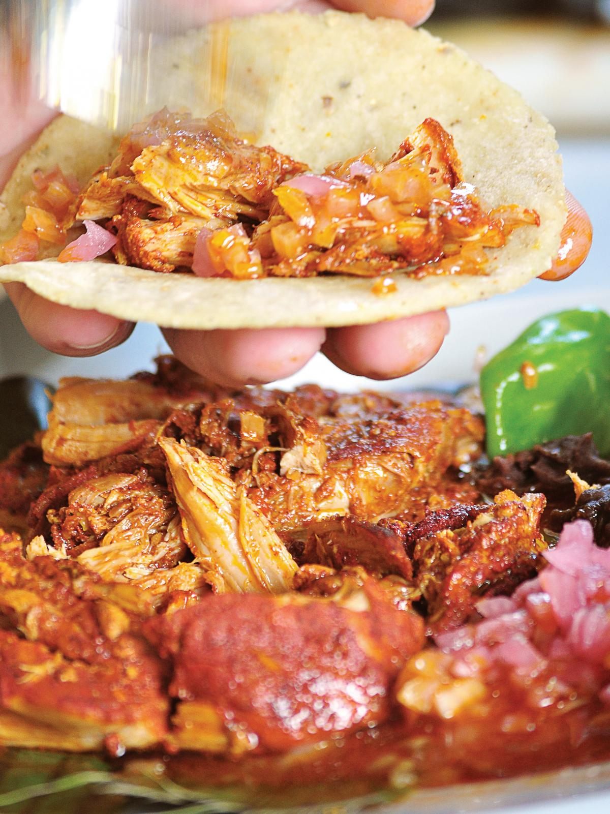 "The name of these tacos, ""cochinita pibil,"" tells you what's inside: young pig cooked in an oven pit. It's a traditional Mayan dish that originated after the Spanish conquistadors arrived, bringing pigs with them."