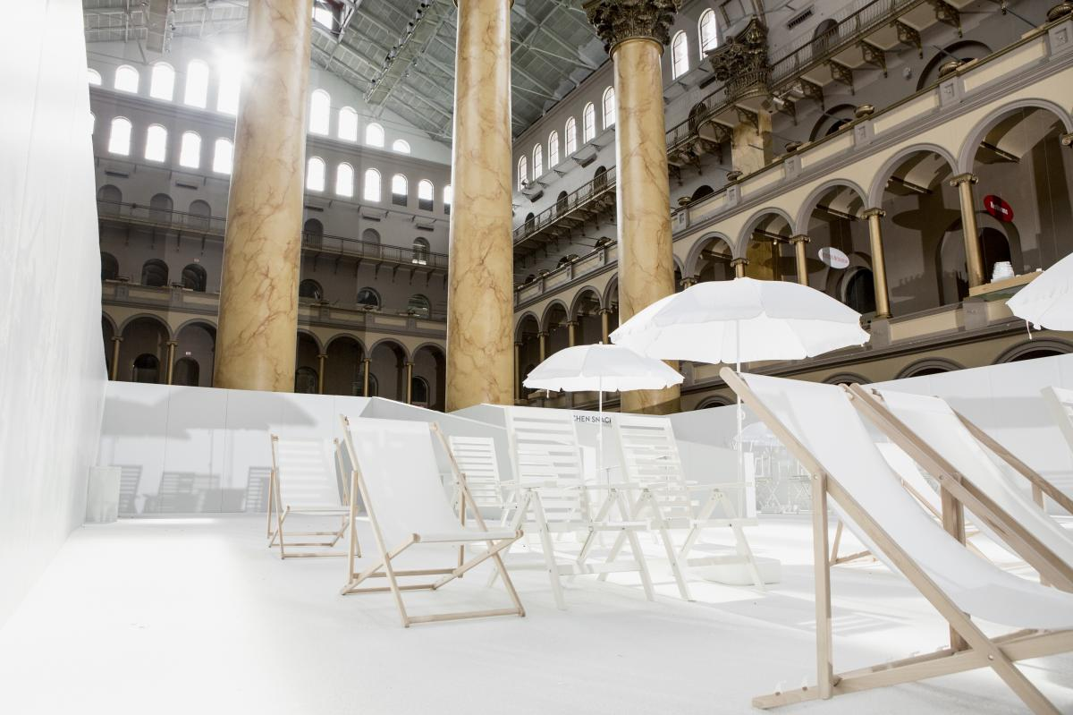 The exhibition includes lounge chairs and 700,000 white plastic orbs in the museum's Italian Renaissance style building.