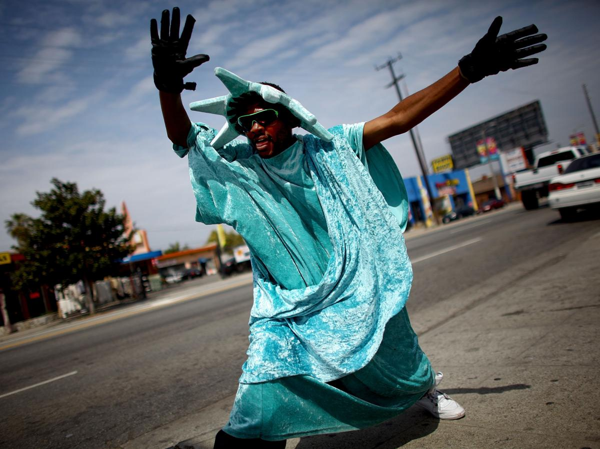 Robert Oliver, 27, dances on the corner of 28th and Crenshaw in west Los Angeles, dressed in a Statue of Liberty costume outside the offices of Liberty Income Tax.