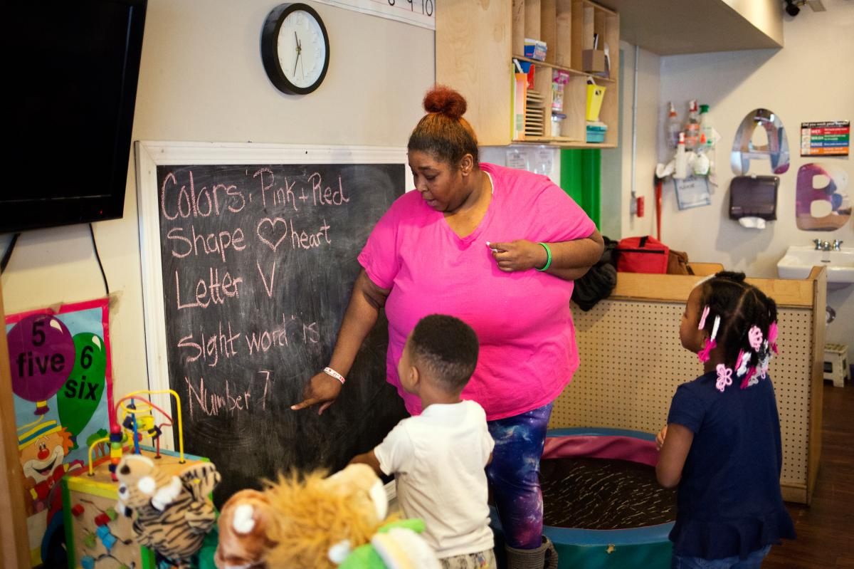 The program's assistant director, Tawanda Brand, works with students at the Little Explorers Learning Center in St. Louis on Jan. 29. After closing temporarily because of the coronavirus, the center re-opened in May for the children of essential workers.