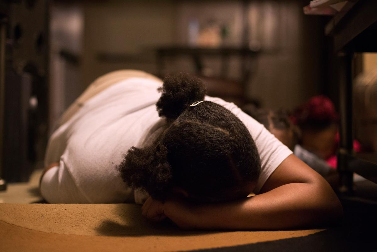Anajah Hicks, 13, demonstrates the position she's been taught to take when she hears gunshots. Her mom and grandmother make sure the teen and her siblings practice getting on the floor quickly to stay safe.