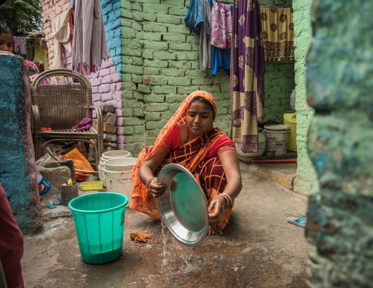 Shakuntala Devi, 26, a mother of three, washes dishes in the courtyard of her home in a crowded slum near the American Embassy School in New Delhi. Her home has no running water, so Devi has to fetch water in jerrycans from a government tanker truck.