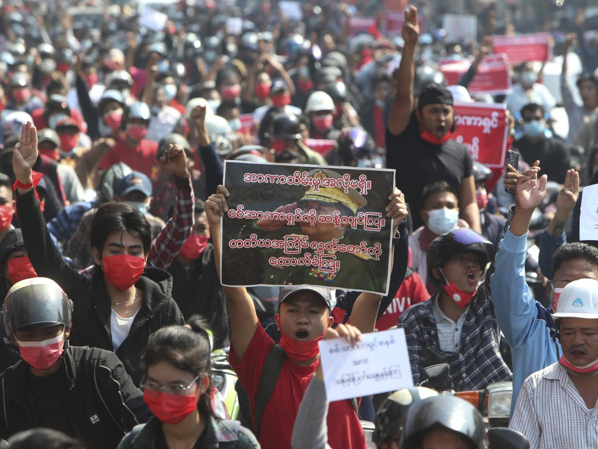 A protester shouts slogans while holding a placard with an image of Myanmar military Commander-in-Chief Senior Gen. Min Aung Hlaing as fellow protesters march around Mandalay on Sunday.