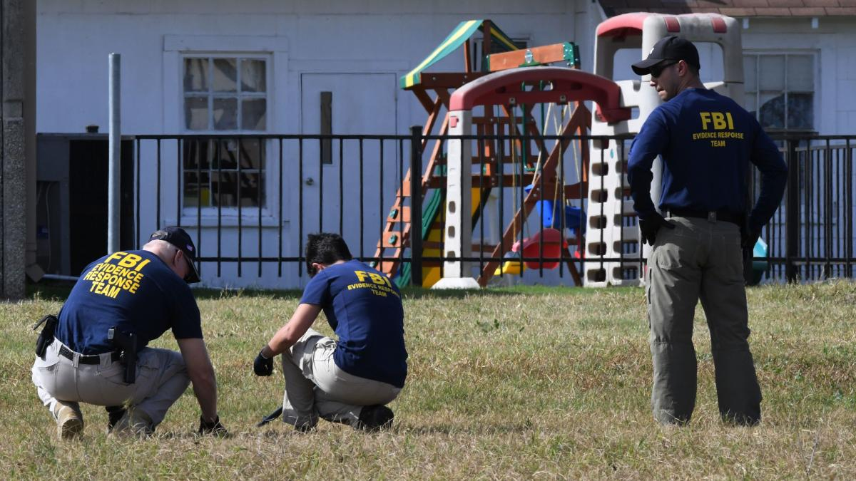 FBI agents search for clues Monday beside a playground near the First Baptist Church in Sutherland Springs, Texas.