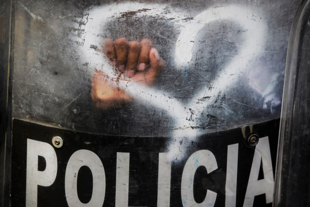 With heart-shaped graffiti spray-painted by activists on a shield, Nicaraguan riot police stand by in August 2019 as anti-government protesters in Managua call for the reinstatement of health workers who lost their jobs for assisting protesters during a d