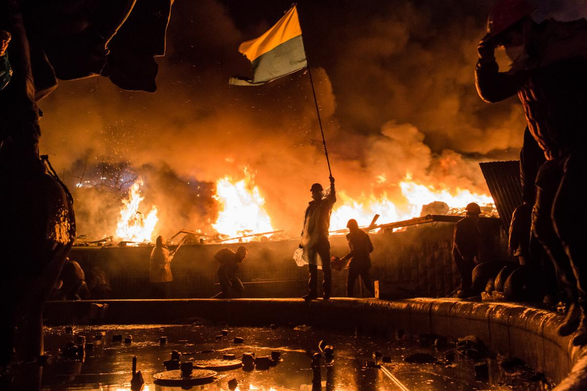 Amid fires set around Independence Square, known as the Maidan, in Kyiv, Ukraine, protesters demonstrate against the government of then-President Viktor Yanukovych in February 2014. Protesters called for Yanukovych's ouster over allegations of corruption