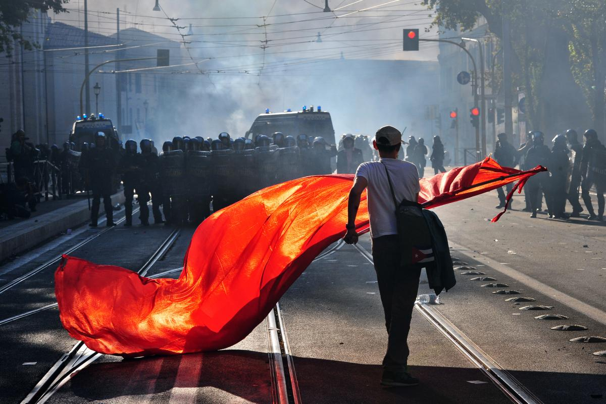 A protester waves a red flag in front of anti-riot police in Rome in October 2011. Tens of thousands marched as part of a global day of protests inspired by Occupy Wall Street.