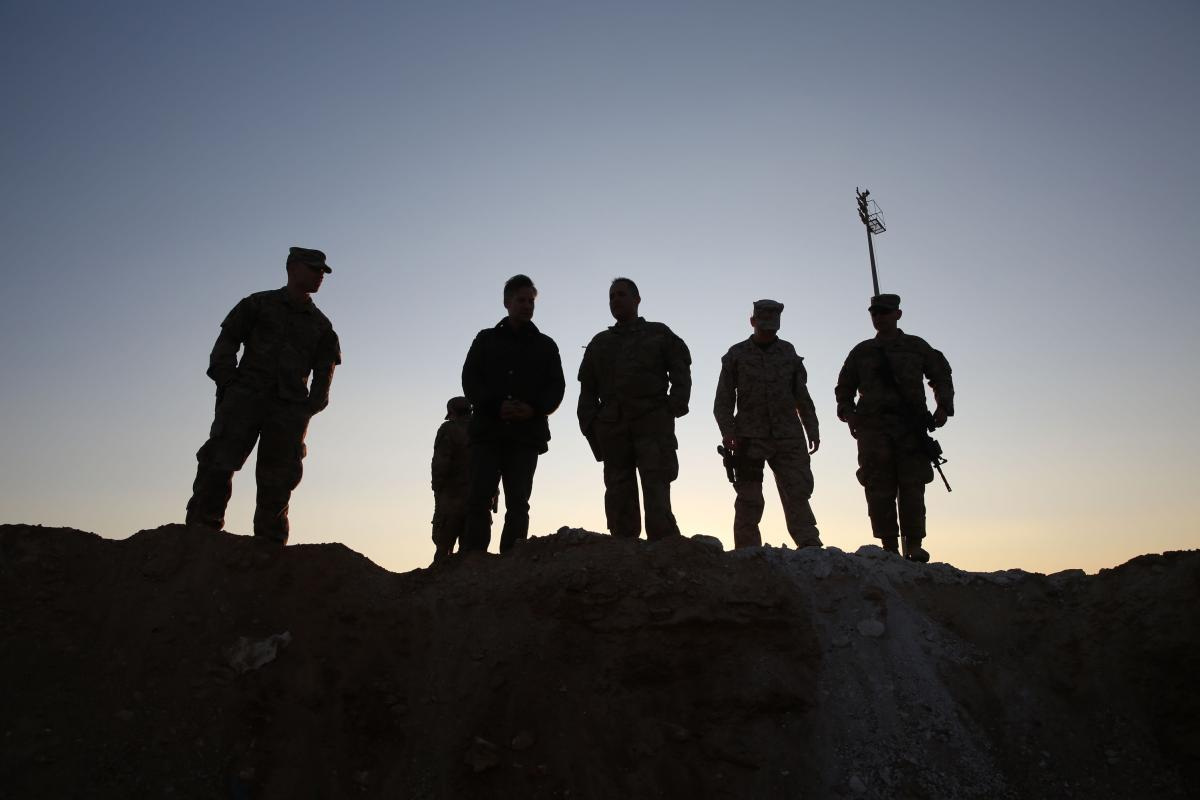 U.S. service members stand at Ain al-Assad base at dusk on Monday.