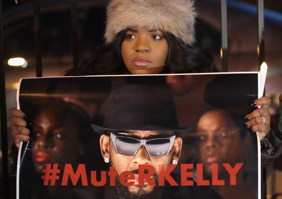 """A demonstrator holds up a sign reading """"#MuteRKelly"""" at a protest outside the singer's Chicago studio in January 2019, just days after the release of the Lifetime mini-series Surviving R. Kelly."""