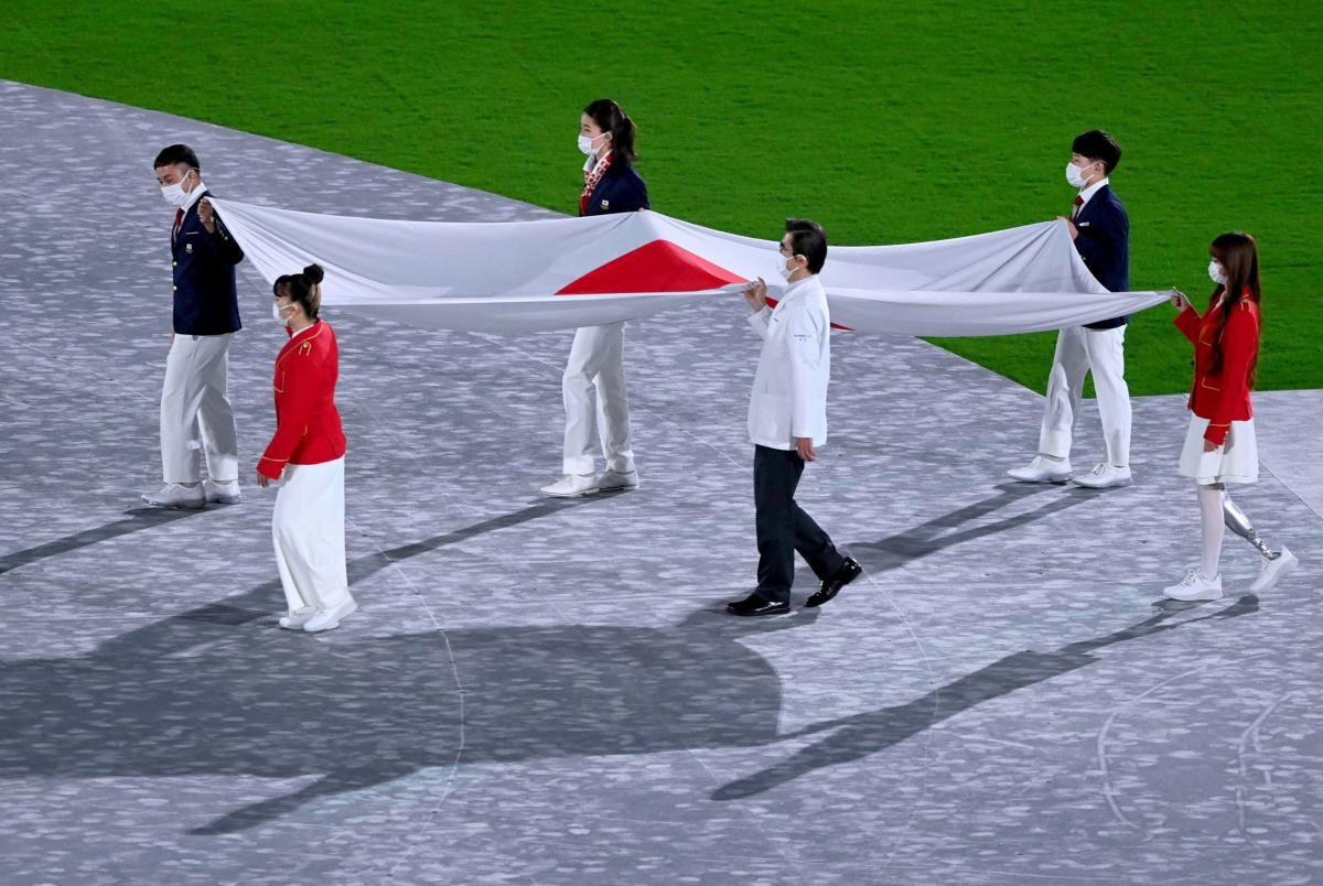 The Japanese flag is brought into the stadium.
