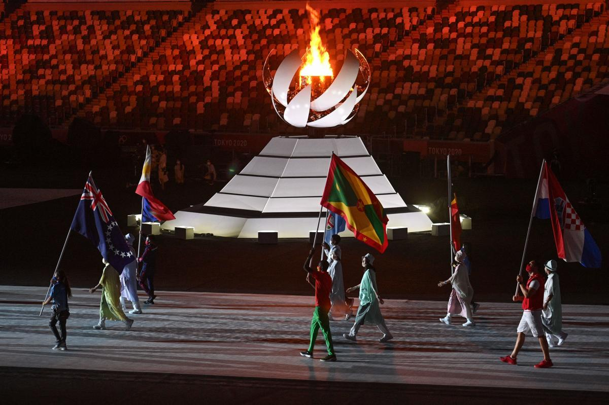 Athletes carrying nations' flags walk past the Olympic flame as they enter the stadium during the closing ceremony of the Tokyo 2020 Olympic Games.
