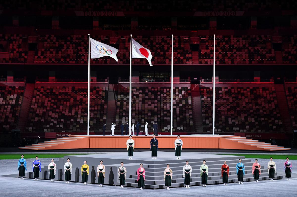 Performers sing the Japanese national anthem as the Olympic flag and Japan's flag are raised.