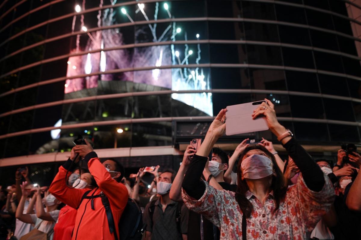 Bystanders take images of fireworks lighting up the sky over the Olympic Stadium.