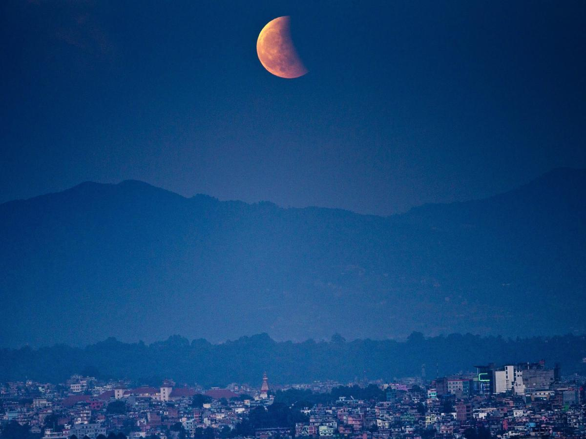 The moon glows red as it rises during a total lunar eclipse as seen in Kathmandu, Nepal.