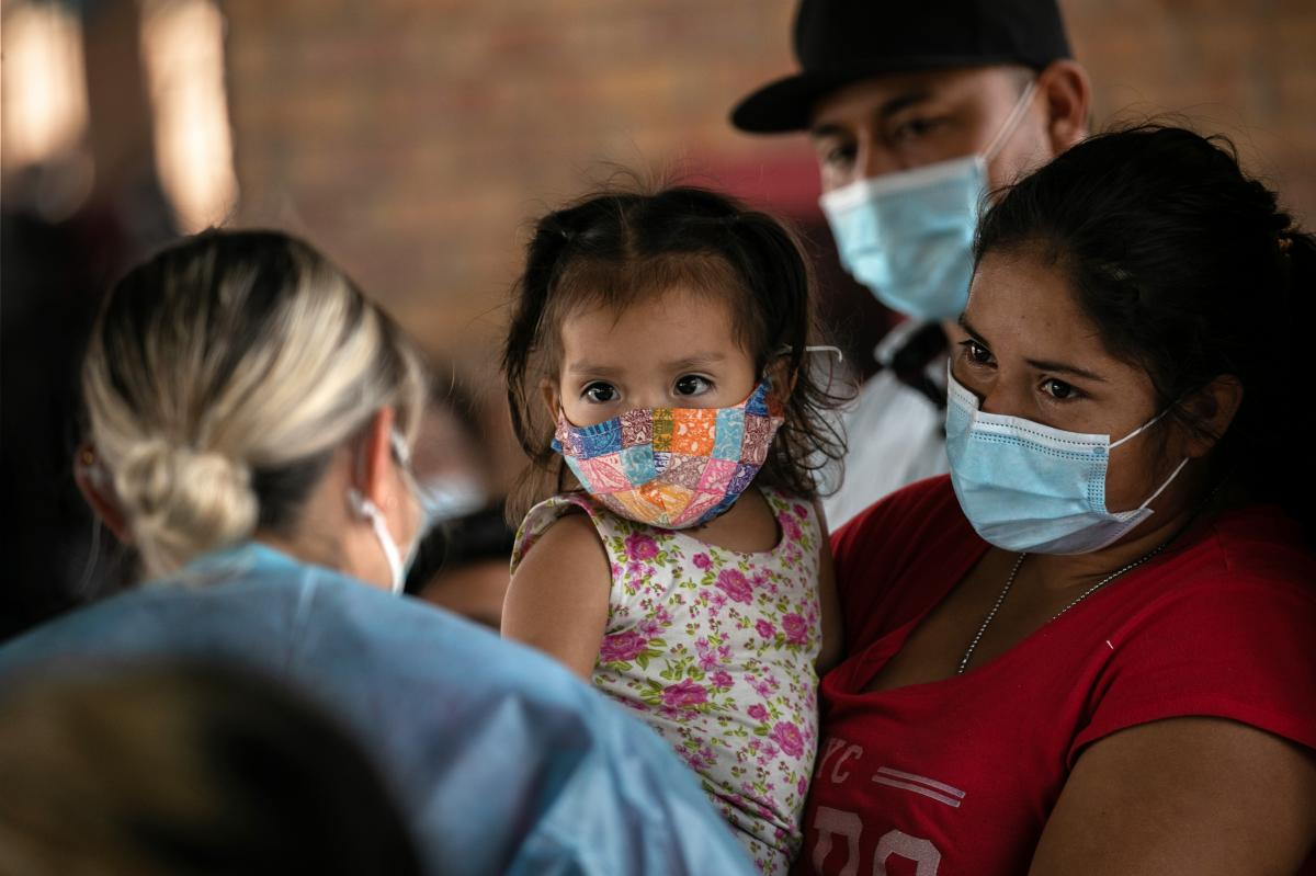 A mother holds her daughter while awaiting COVID-19 test results last month after being released by U.S. immigration authorities in Brownsville, Texas.