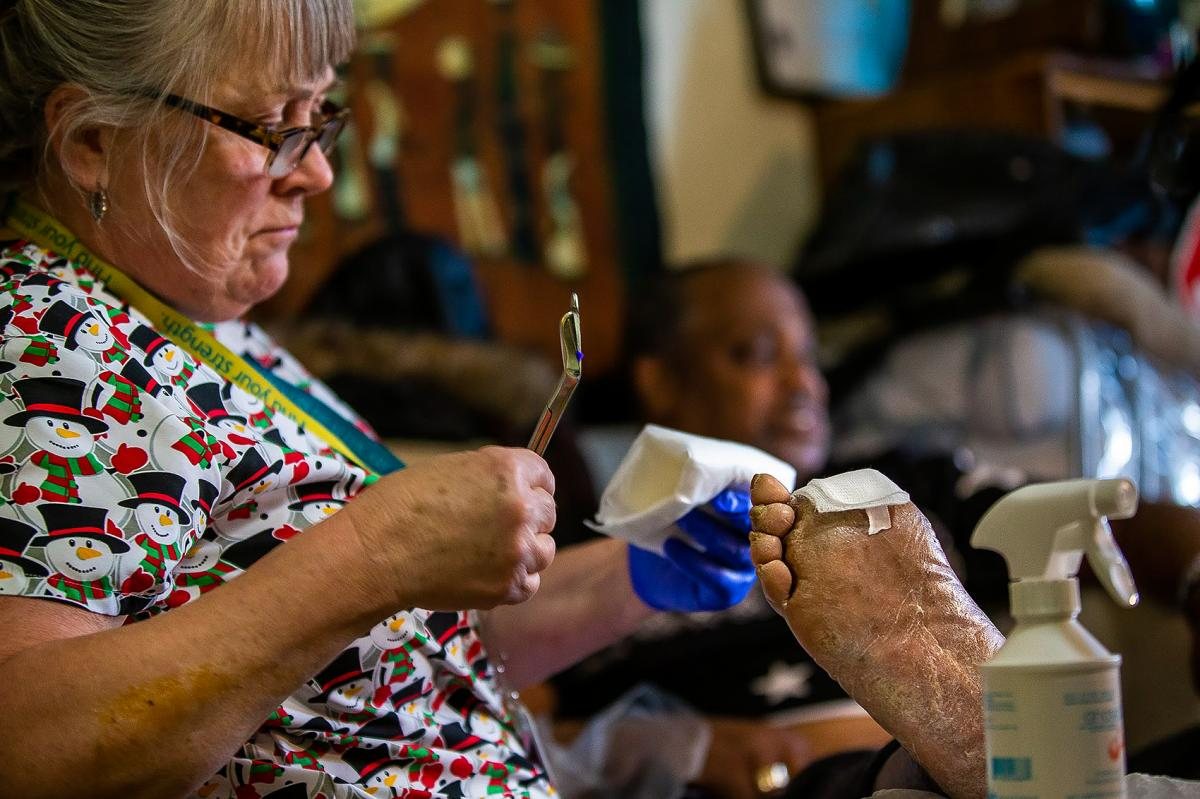 """Nurse Mastricola tends to the still-healing wound on Arthur Jackson's foot. He says his doctor initially worried he might be enticed to use the IV line to once again turn to heroin. But he's been taking burprenorphine for two years, to prevent that. """"I'm"""