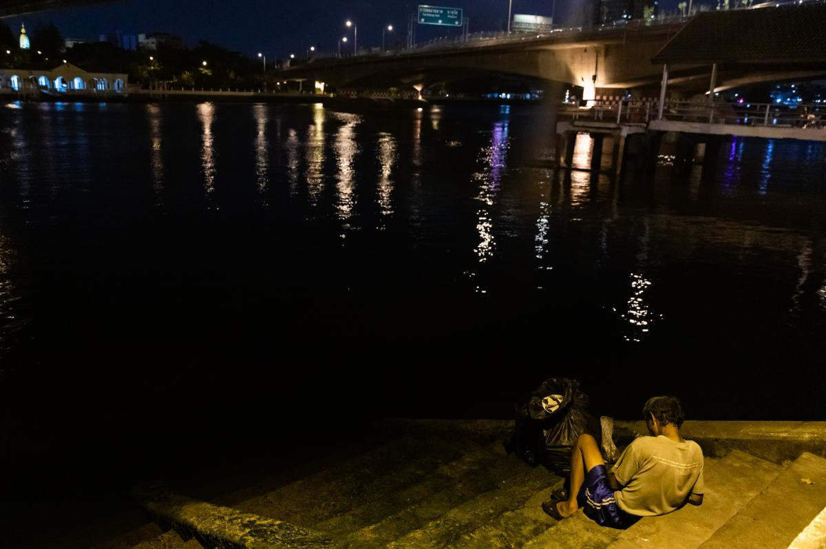 A man rests under the Memorial Bridge, which spans the Chao Phraya River in Bangkok.