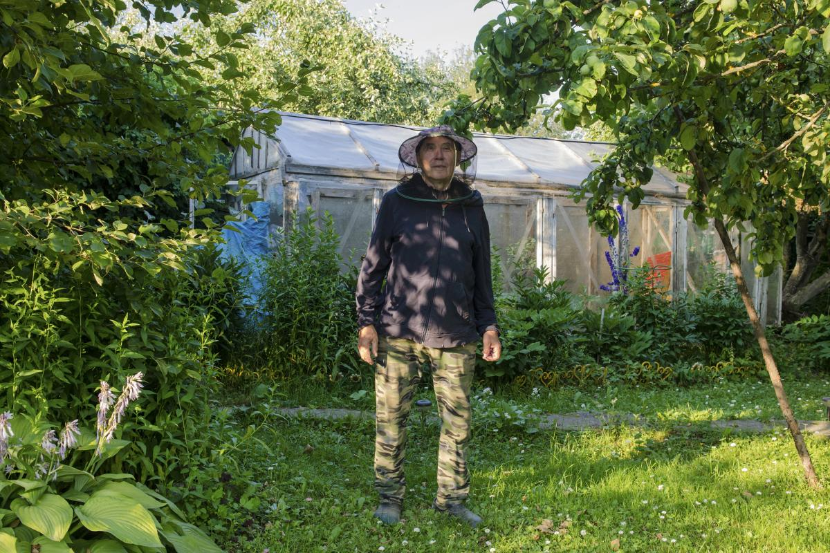 """Vladimir wears protective netting against horse flies. He says his two sons rarely visit. """"The dacha isn't for everyone,"""" he admits."""