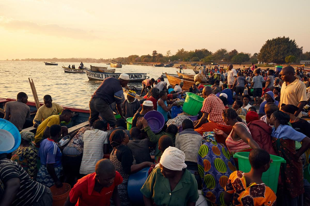 A crowd of fish traders forms around a boat at Lake Malawi laden with usipa, a species of small sardine-like fish that are dried and sold all over the country.