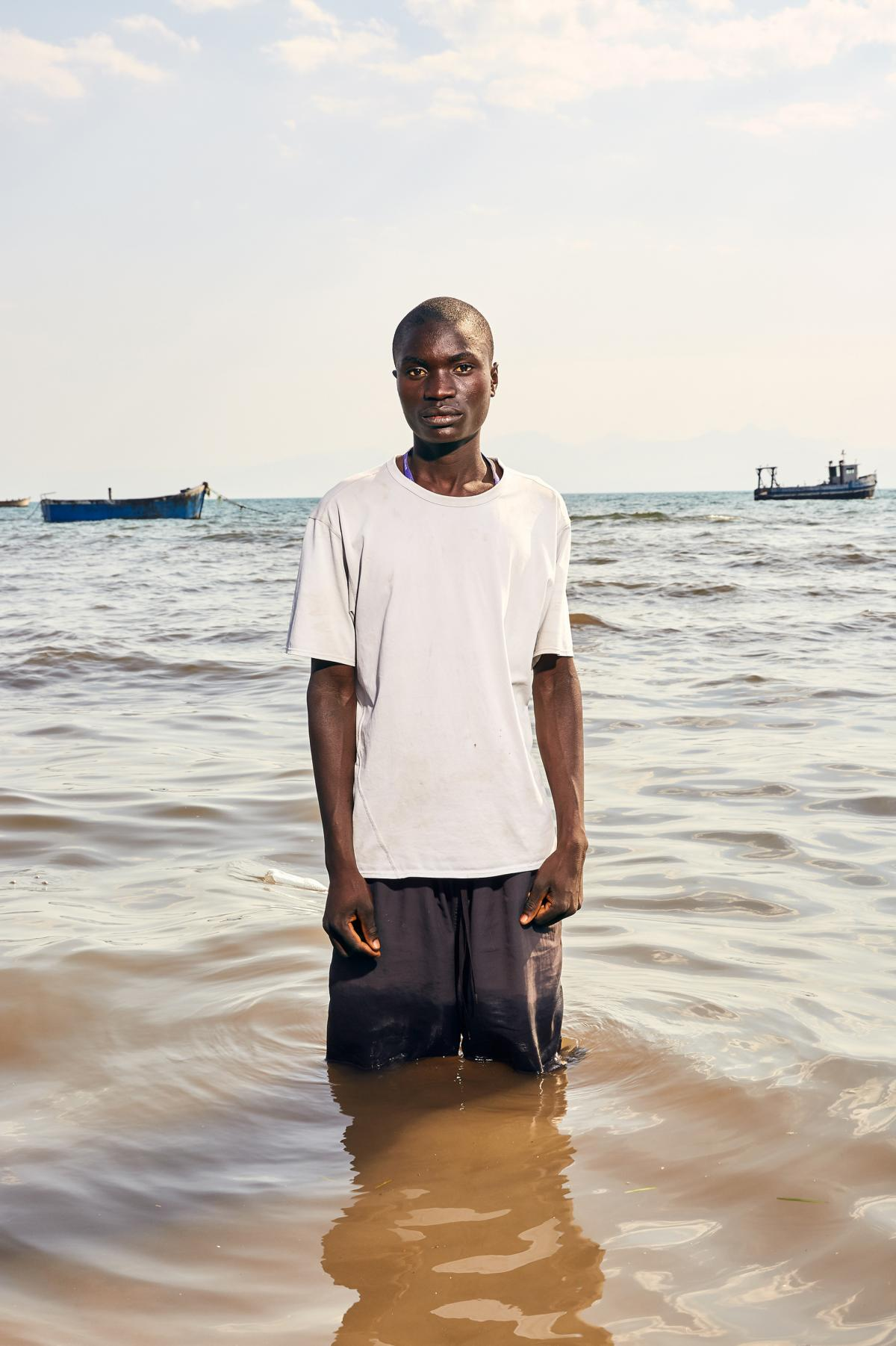 "Fisherman Mekius Dominic stands in Lake Malawi. Dominic became a fisherman three years ago. He says he has never engaged in transactional sex but knows plenty of men who do. ""My friends have said to me that I must do it. They force me to come with them an"