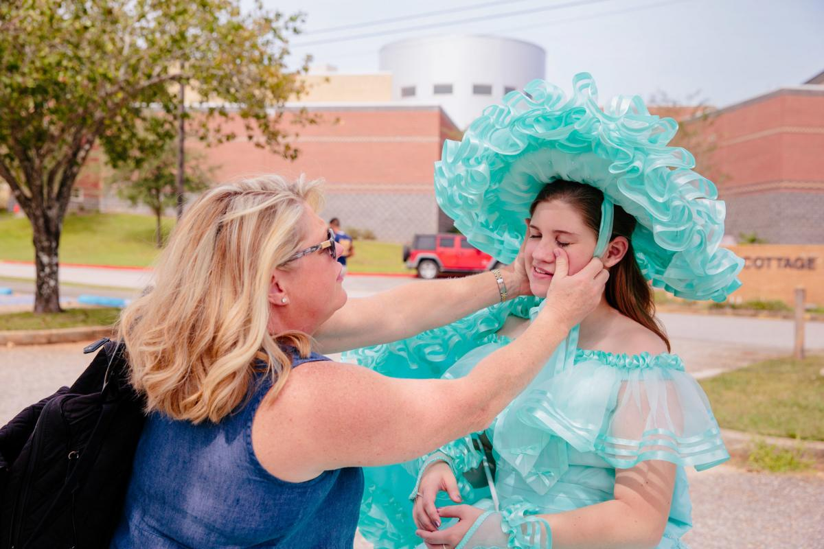 Ellie's [last name not given] mom, who was also a Trail Maid, helps her get ready before an appearance at her high school's homecoming parade.