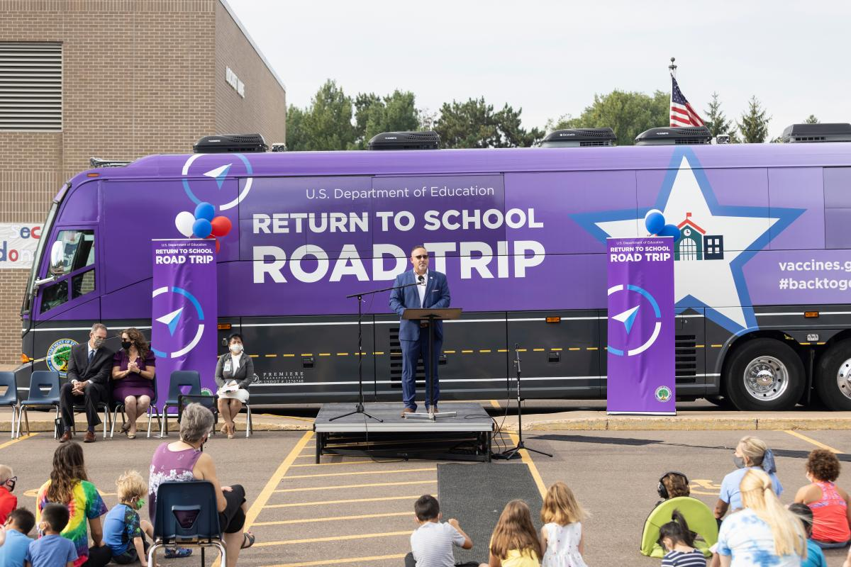 """Cardona addresses students and staff during the Locust Lane pep rally. Eau Claire was the first stop of the secretary's """"Return-to-School Road Trip,"""" which took him to five Midwestern states this week in a lush, purple bus."""