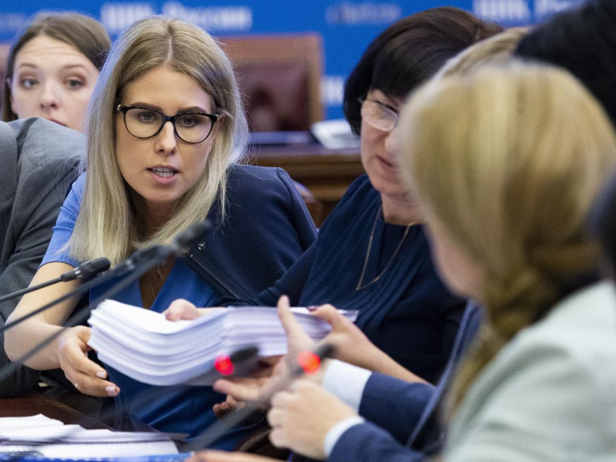 Sobol (left) gives election documents to Ella Pamfilova, head of the Russian Central Election Commission (right, back facing camera), during a meeting with opposition candidates at the commission in Moscow on July 23.
