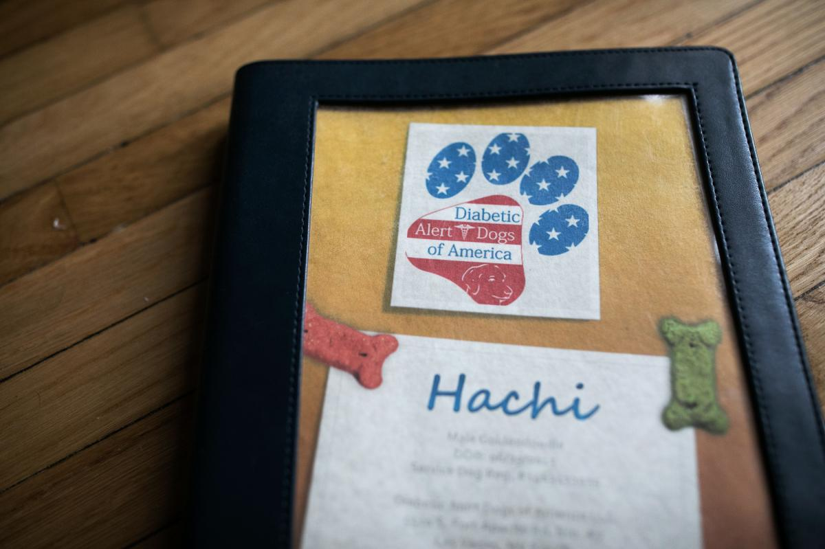 A book from Diabetic Alert Dogs of America sits in the home of Jessica Moye, who purchased her dog Hachi from the company.