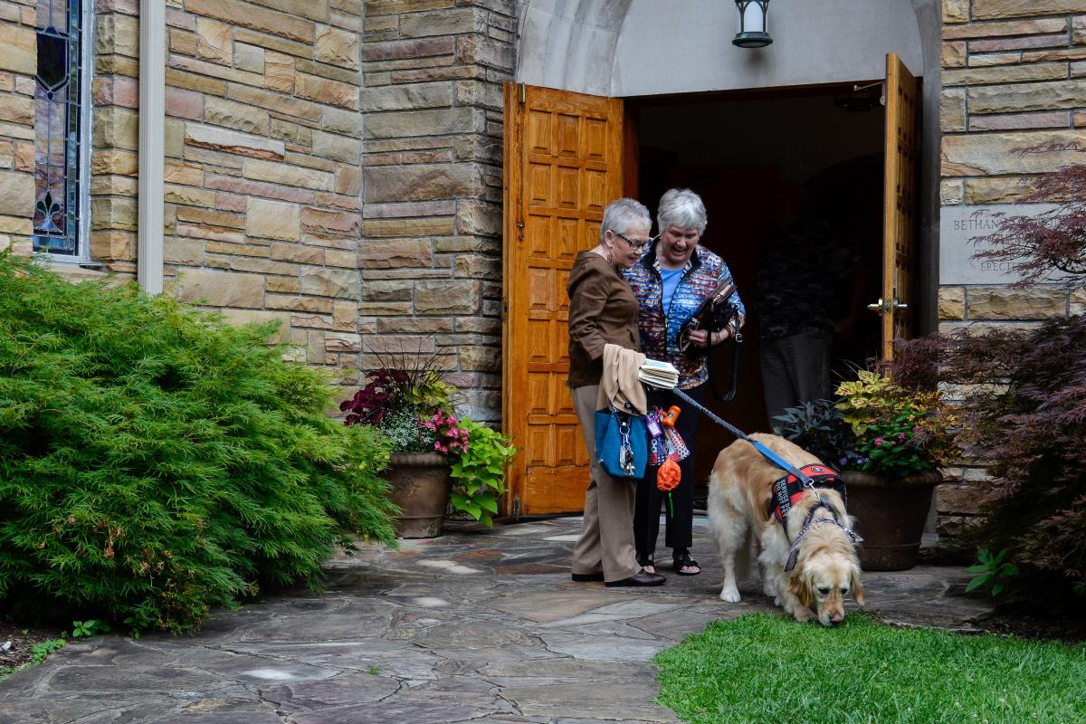 Peggy Gibson (left) guides her diabetic alert dog Rocky outside as she talks with a friend following a church service at Bethany United Methodist Church in West Jefferson, N.C., on July 7, 2019. The congregation helped Gibson raise the money to purchase R