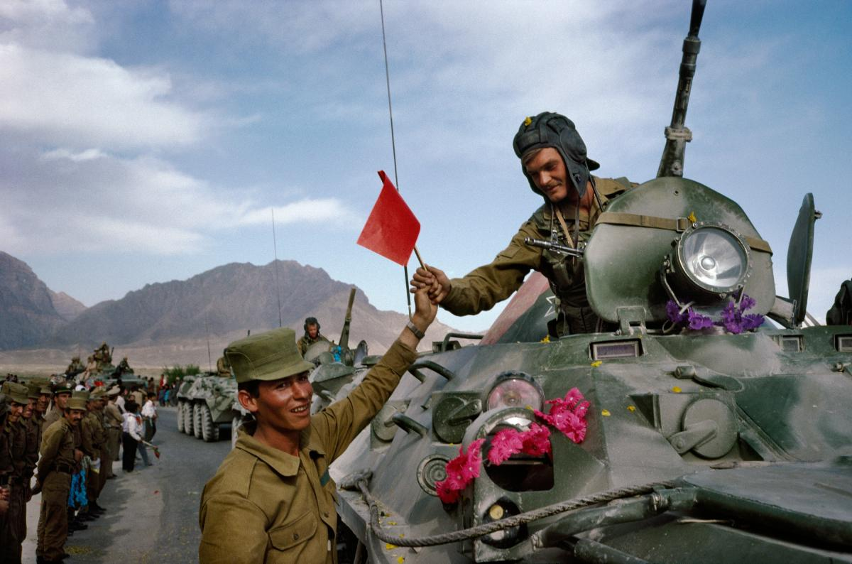 "On the first day of the Soviet withdrawal from Afghanistan in May 1988, an Afghan soldier hands a flag to a departing Soviet soldier in Kabul. ""This was the first time journalists had full access to Kabul,"" Robert Nickelsberg says. It marked his first yea"