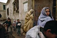 A Kabul family flees its home during factional fighting in March 1993.